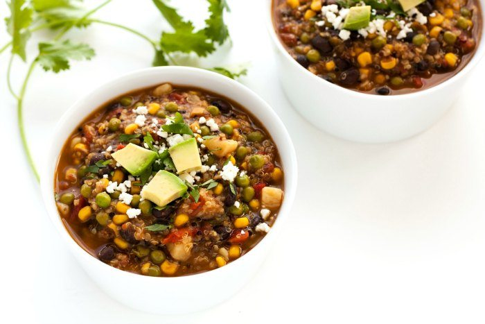 2 bowls of quinoa stew that is topped with cilantro, avocado, and queso fresco.