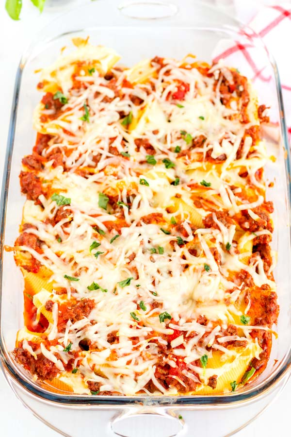 A 913-inch pan of stuffed shells with meat sauce and shredded cheese.