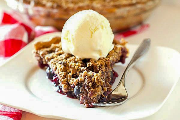 Cherry pie on a white plate with a fork