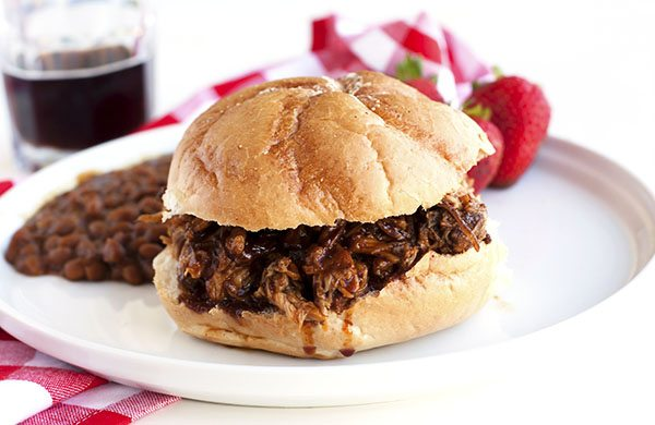 Close up picture of a pulled pork sandwich on a white plate.