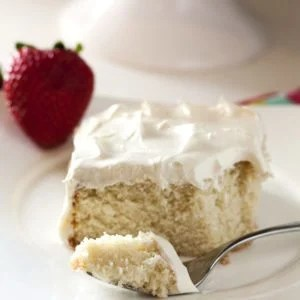 A slice of Emergency White cake with Buttercream frosting on a plate