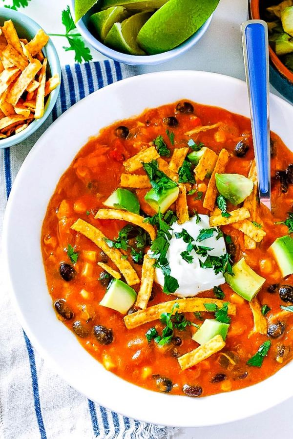 Overhead picture of enchilada soup garnished with sour cream, tortilla strips, and avocado.
