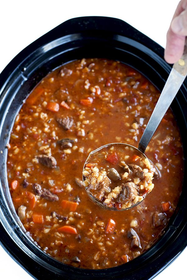 A ladle full of slow cooker beef and barley soup.