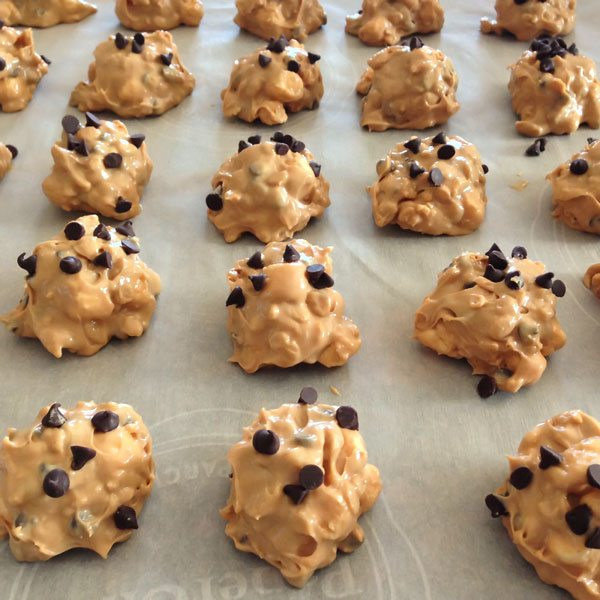 Avalanche cookies freshly scooped onto parchment paper.