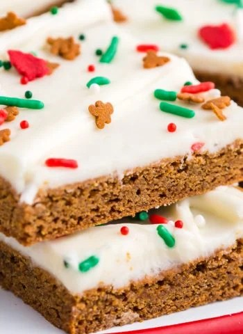 A close up picture of a gingerbread bar with cream cheese frosting and Christmas sprinkles.