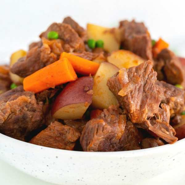 Beef stew in a white serving bowl.