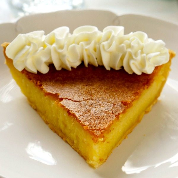 A single piece of buttermilk pie with whipped cream.