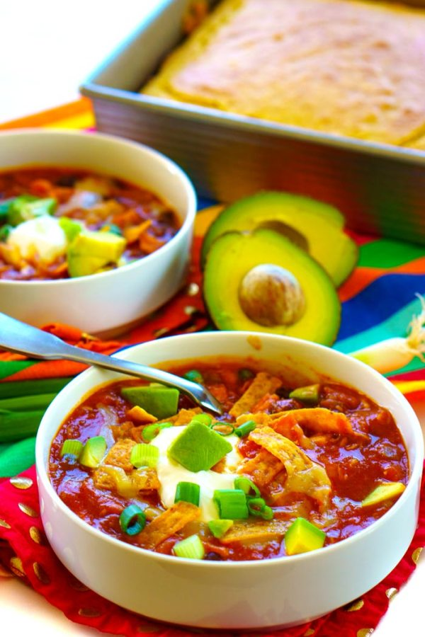 2 bowls of chicken taco soup with cornbread in the background.