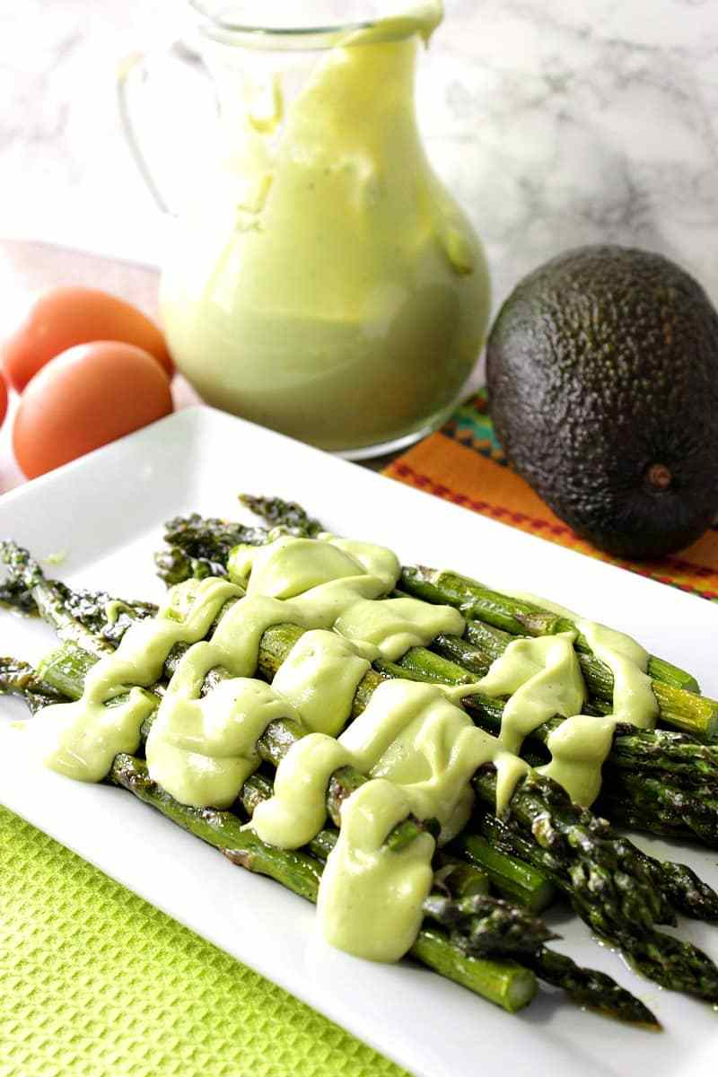 Roasted asparagus with avocado hollandaise sauce on a serving platter