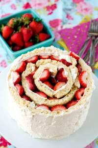 Rolled Up Strawberry Shortcake Cake on a white cake pedestal.