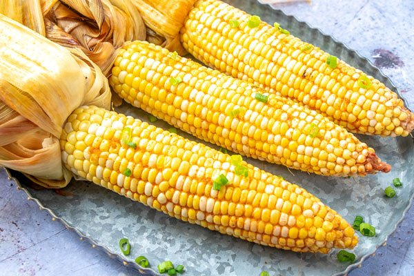 3 pieces of smoked corn on a galvanized tray.