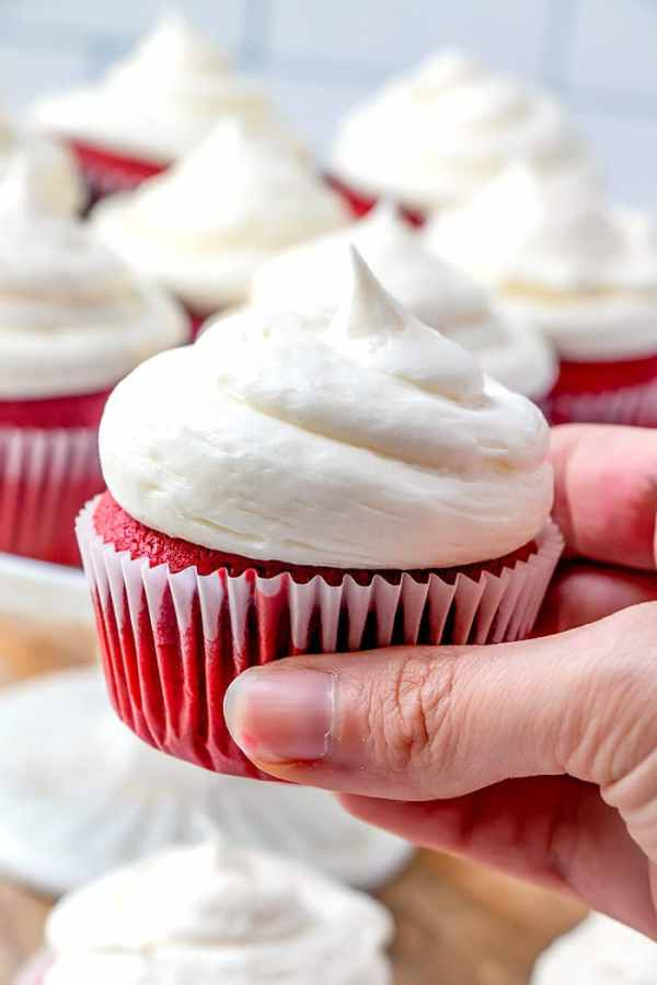 A hand holding a delicious homemade red velvet cupcake.