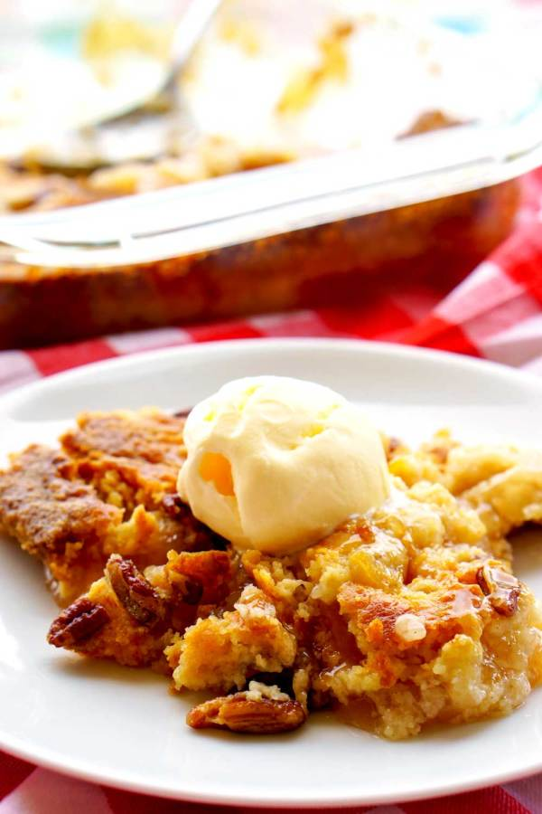 Apple dump cake on a white plate with a scoop of vanilla ice cream on top.
