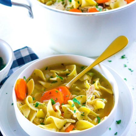 Rotisserie Chicken Noodle Soup recipe in a white bowl with a golden spoon.