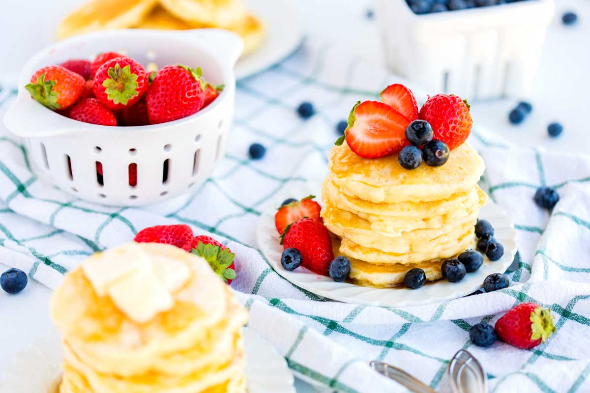 A stack of buttermilk pancakes with fruit on top