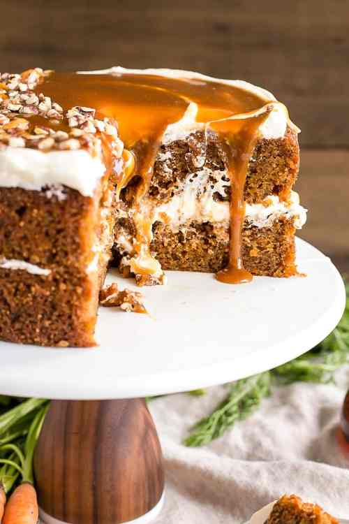 Layered round carrot cake with caramel dripping off of it.