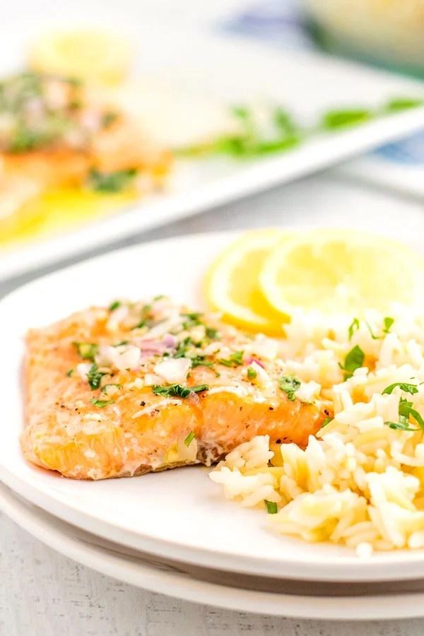 Salmon fillet on a white plate that's topped with lemon vinaigrette.