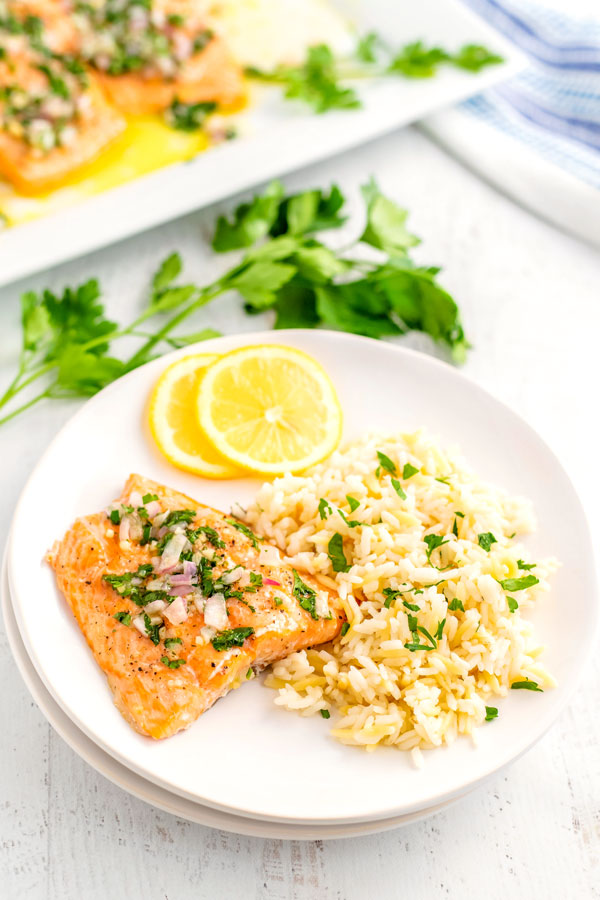 A white dinner plate with baked salmon, rice pilaf, and lemon slices on it.