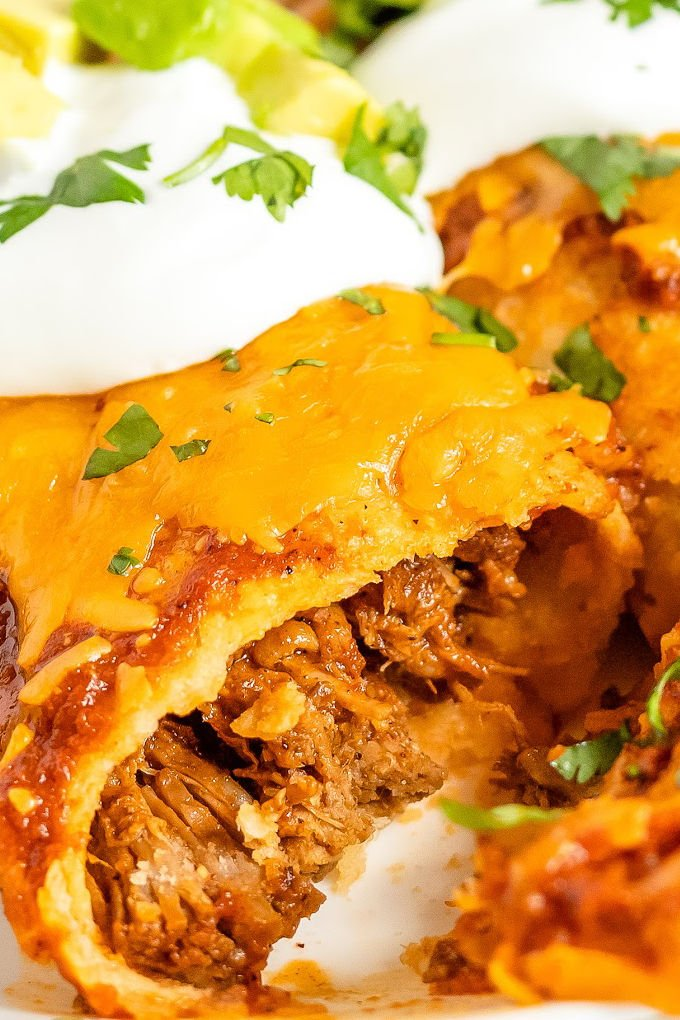 A close up picture of a shredded beef enchilada.