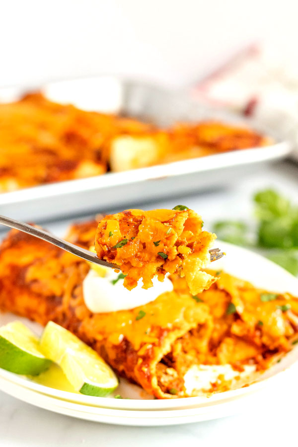 2 rolled enchiladas with a forkful of enchiladas.