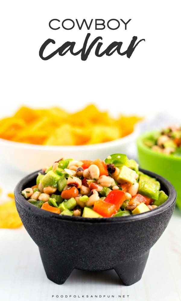 Cowboy caviar in a small black bowl with chips in the background.