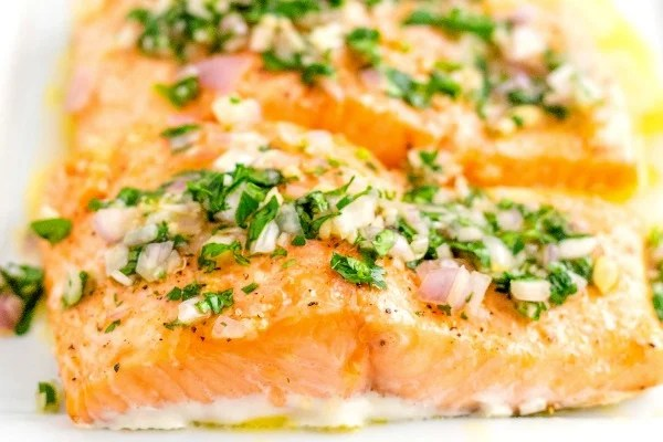Close up picture of baked salmon with lemon vinaigrette on top.