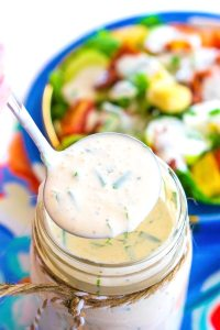 A ladle of buttermilk ranch coming from a mason jar full of dressing.