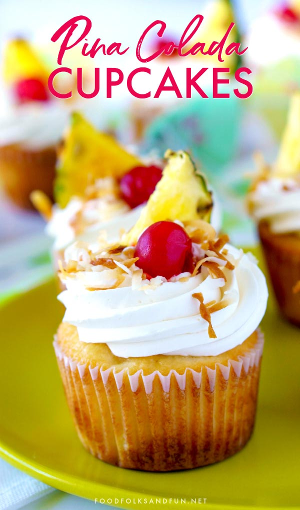 Pina Colada Cupcakes garnished with toasted coconut, pineapple, cherries, and a paper umbrella.