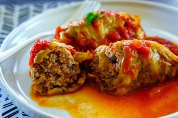 A cabbage roll cut in half to show the cooked filling.
