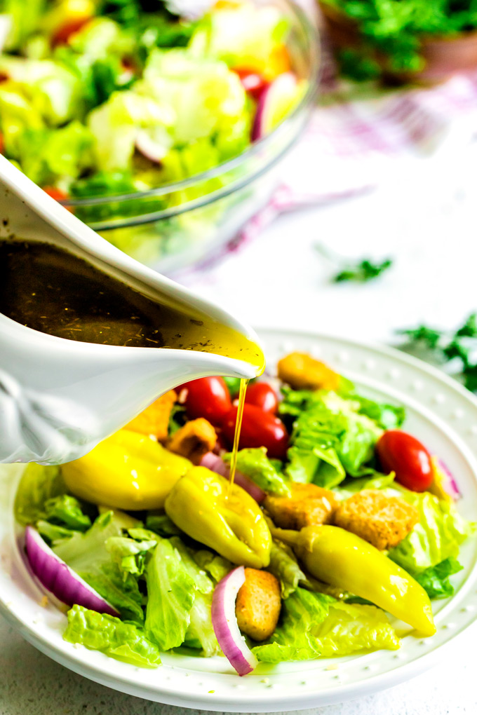 Italian Salad Dressing being poured over a salad.