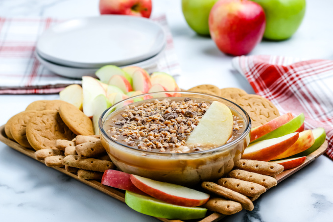 The cream cheese caramel apple dip on a serving platter with apple slices and graham cracker sticks.