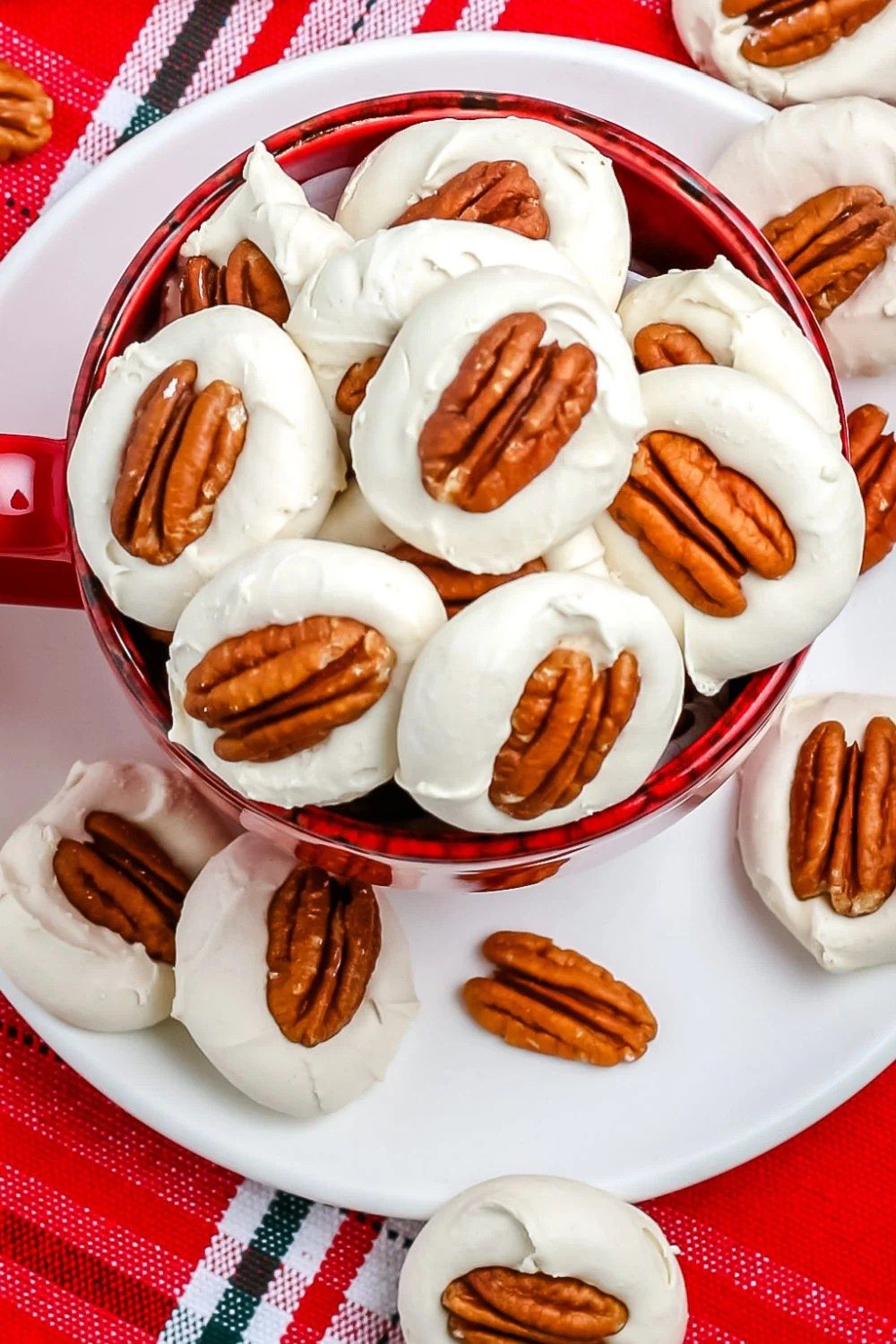 An overhead picture of a platter of divinity candy with pecans on top of them.