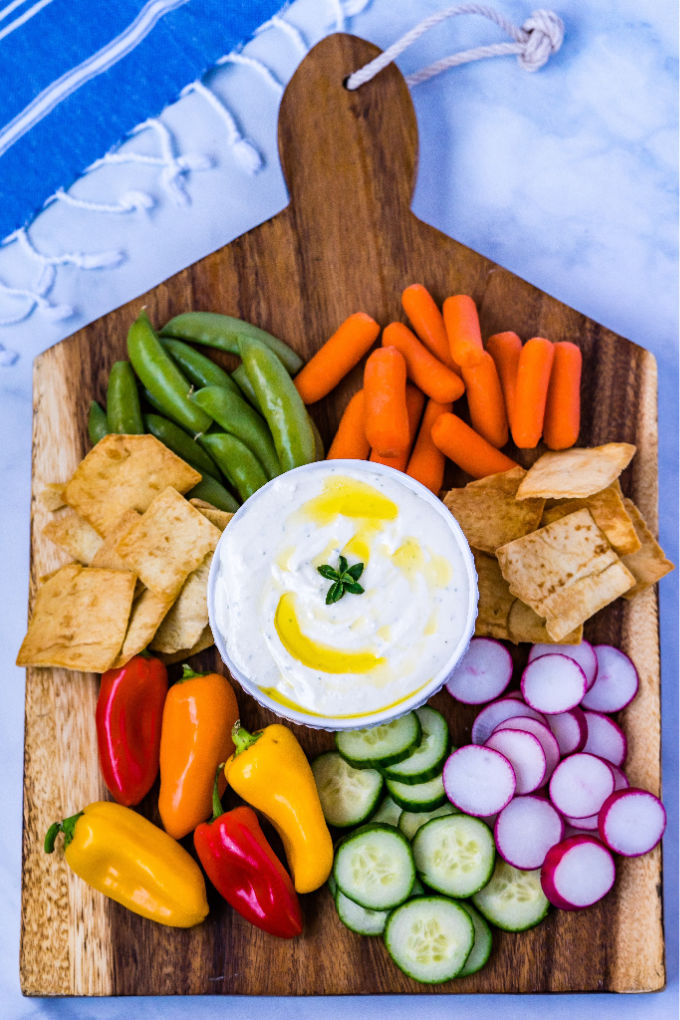 An overhead picture of whipped feta dip in a white bowl surrounded by veggies and pita chips for dipping.