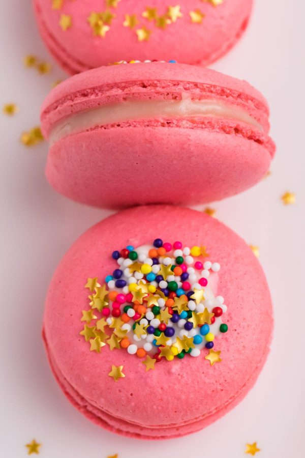 A close up picture of pink macarons on a white plate.