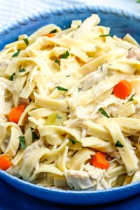 A close up picture of Chicken and Egg Noodles in a blue serving bowl.