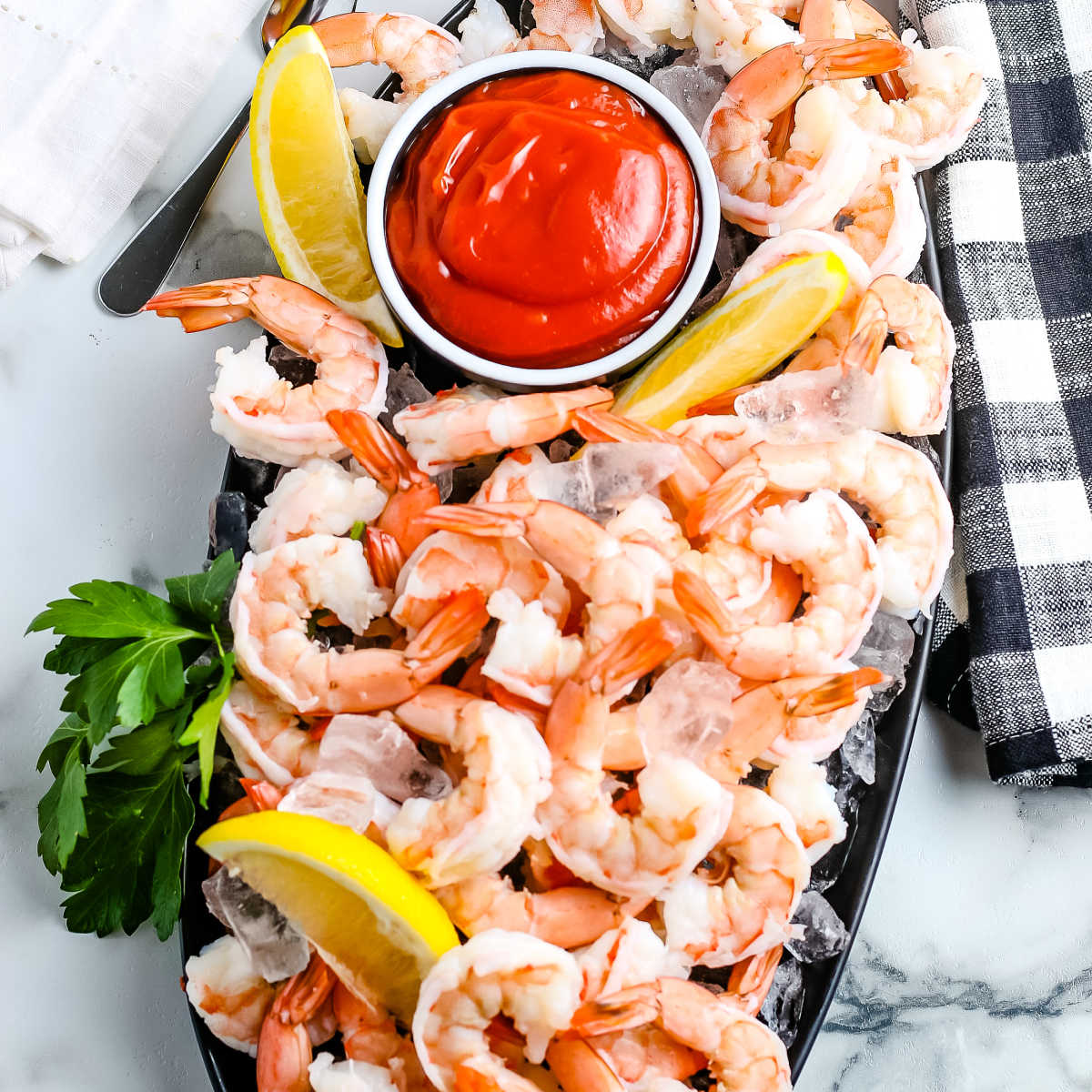 An overhead picture of the finished shrimp cocktail on a black platter.