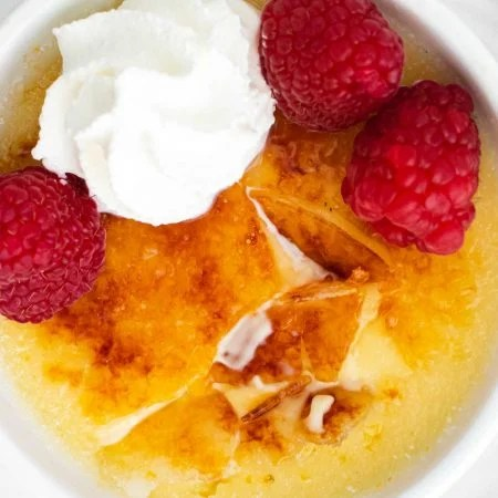 A close up picture of creme brulee with its crackly topping cracked into.