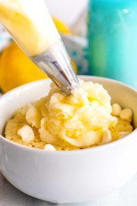 Lemon frosting being pipped onto a lemon mug cake.