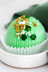 A finished St Patrick's Hot Chocolate Bomb on a plate.