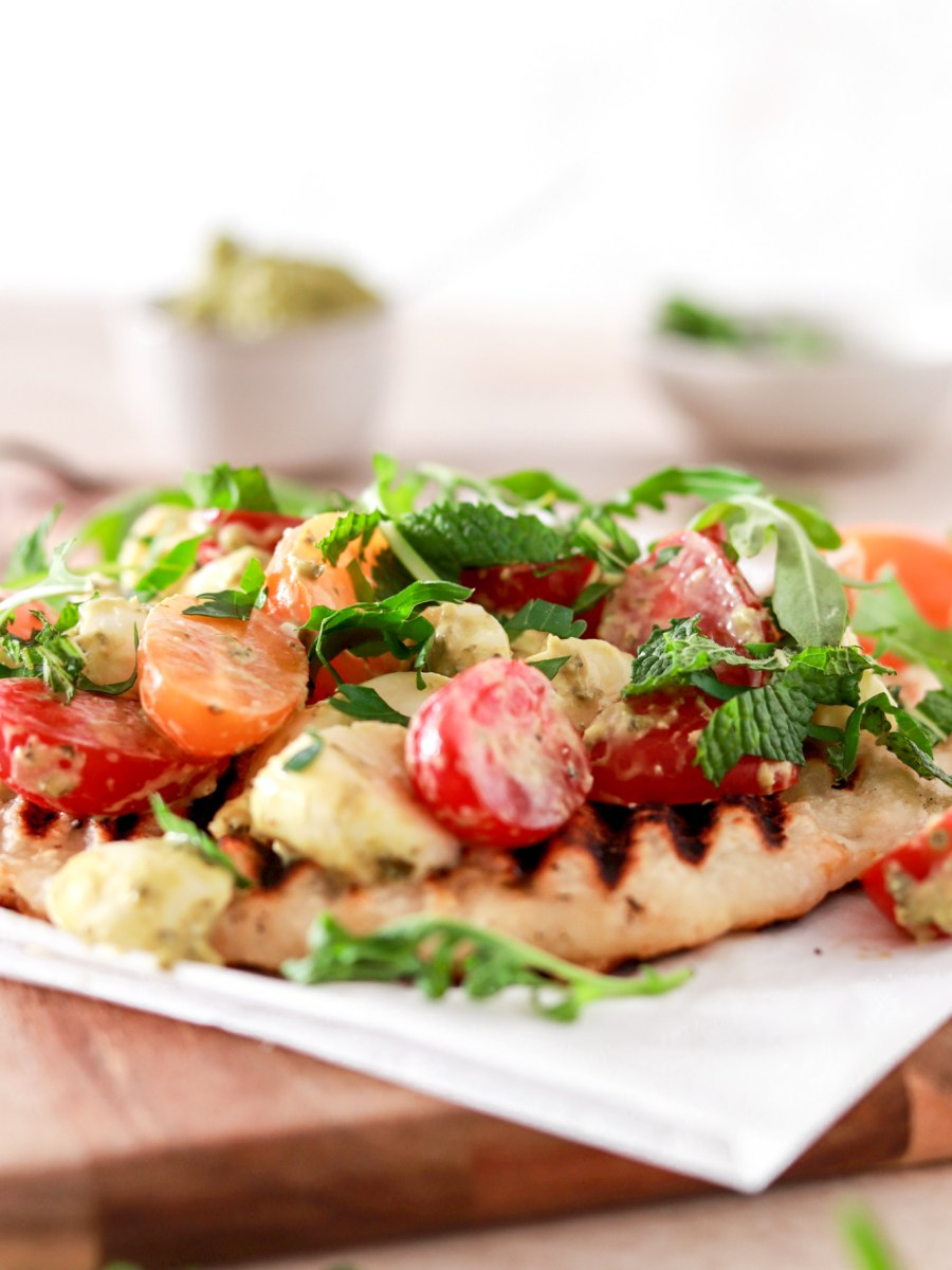 Easy Flatbread Pizza with Cherry Tomatoes, Mozzarella & Pesto (Gluten Free) From Front On Cutting Board