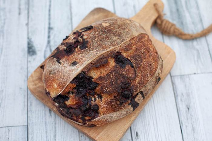 freshly baked blueberry lemon sourdough bread on a cutting board