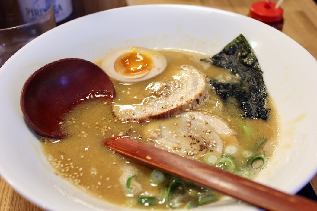 A milky bowl of ramen with a soft boiled egg, seaweed, spring onions and char siu.