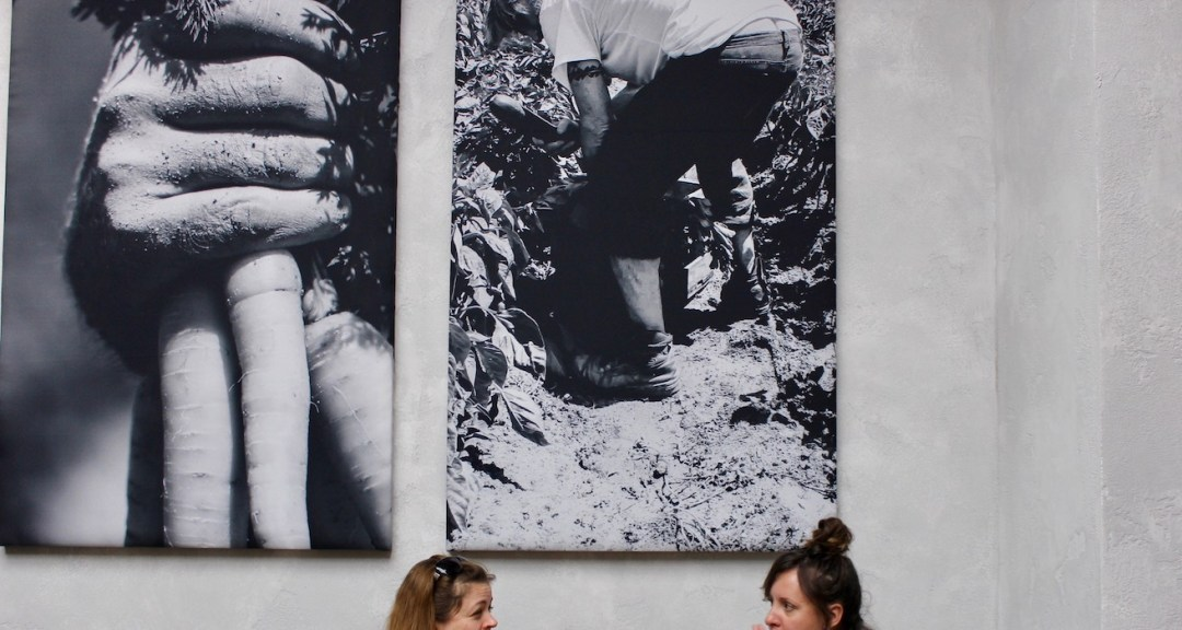 Two women eating under black and white pictures in Honest Greens Barcelona