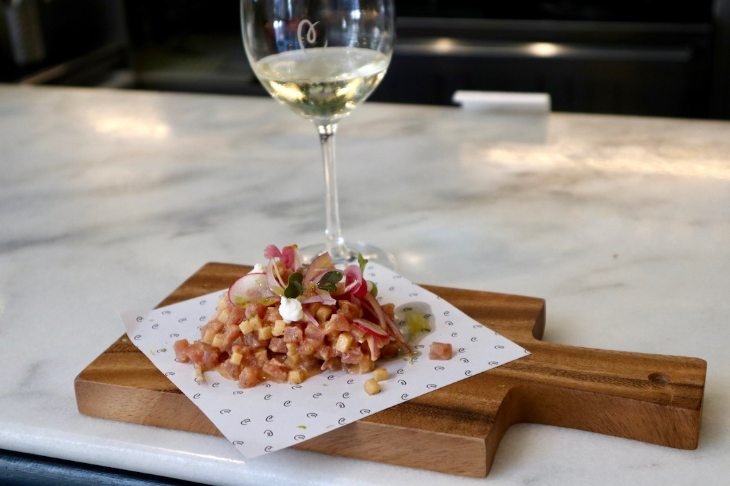 A glass of wine and kimchi ceviche at La Catalista