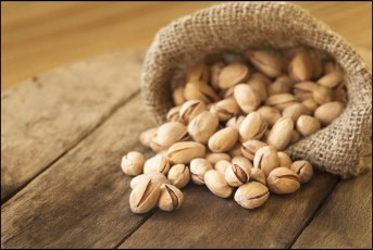 roasted-pistachios-on-natural-wooden-table-background