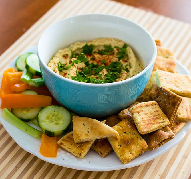 Roasted garlic hummus with black pepper pita chips is a healthy snack.