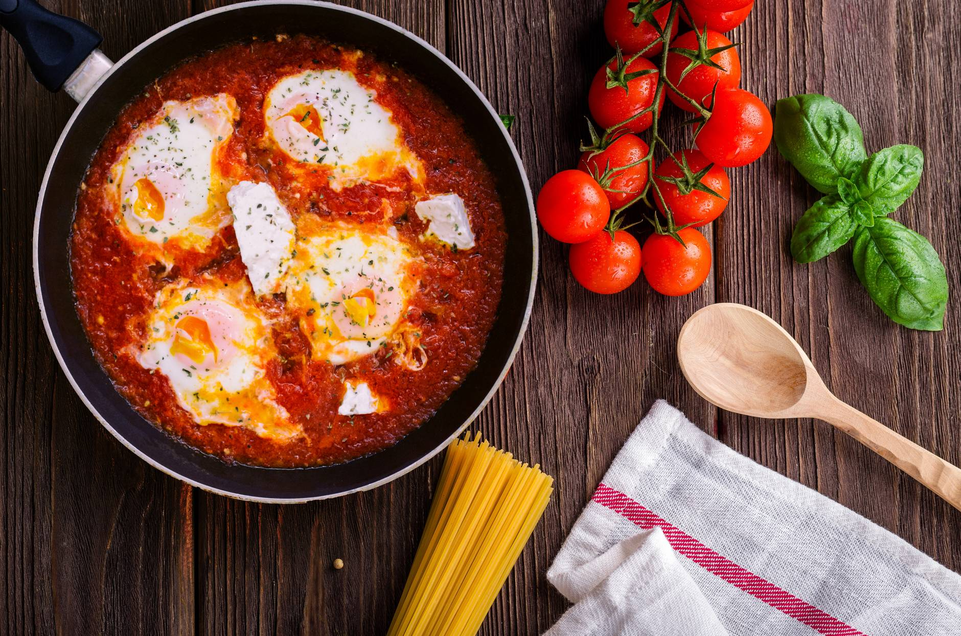black frying pan with spaghetti sauce near brown wooden ladle and ripe tomatoes