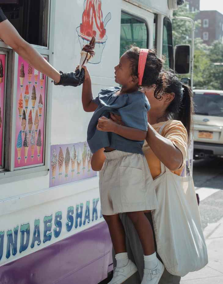 ethnic woman buying ice cream with daughter