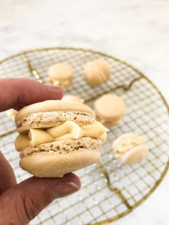 Close of Salted Caramel Macarons Held Between Fingers - www.foodnerd4life.com