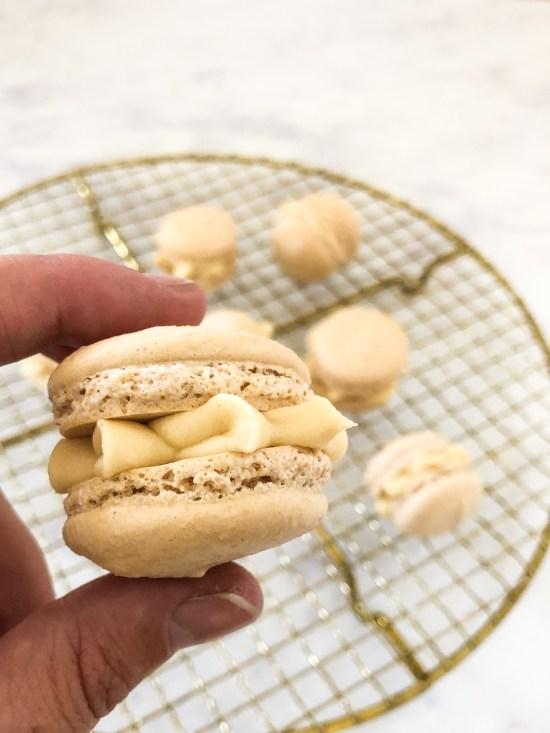 Close of Salted Caramel Macarons Held Between Fingers - www.foodnerd4life.com